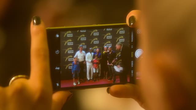 Auf einem Handyschirm ist eine Gruppe von Menschen zu sehen, die auf dem roten Teppich posieren.