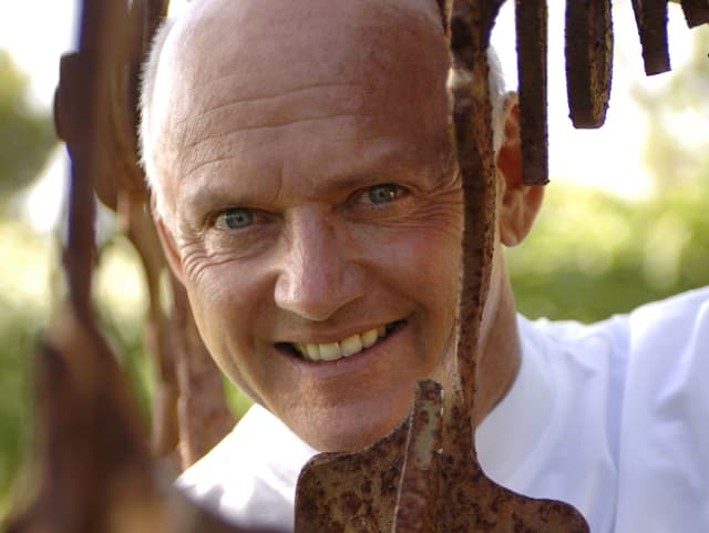 Rolf Knie schaut durch ein Metall-Objekt