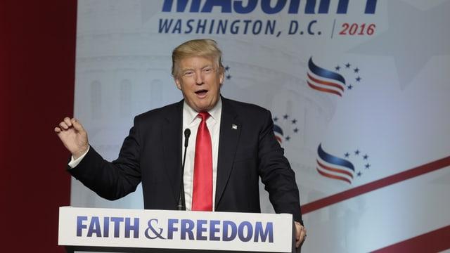 """Donald Trump an einem Rednerpult, auf dem """"Faith & Freedom"""" steht."""
