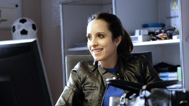 Eine dunkelhaarige Frau mit Lederjacke sitzt lächelnd vor einem Bildschirm.