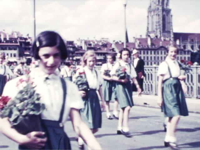 Altes Filmbild: Mädchen marschieren mit Geranien unterm Arm über eine Brücke.