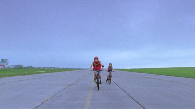 Ein Mann und ein Kind fahren mit dem Velo auf einem abgelegenen Flughafengelände.
