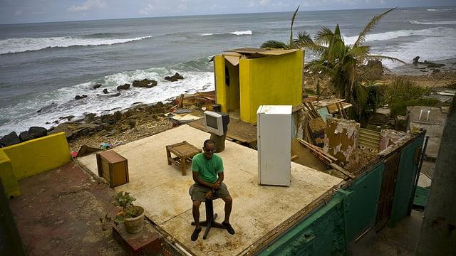 Mann sitzt auf den Trümmern eines vom Hurrikan zerstörten Hauses am Strand