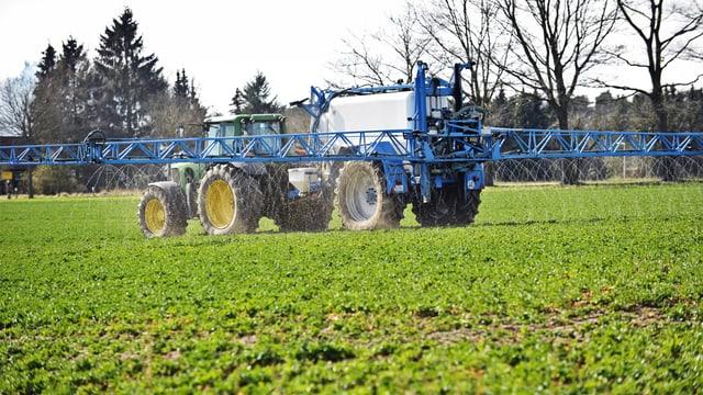 Ein Bauer bringt mit seinem Traktor Unkrautvernichter auf einem Feld aus.