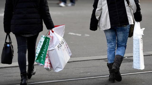 Zwei Personen auf der Strasse beladen mit Einkaufstaschen.