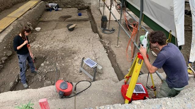 Eine Archäologin und ein Archäologe bei Ausgrabungsarbeiten