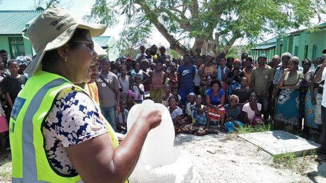 Menschenmenge schaut Frau mit Wasser zu.