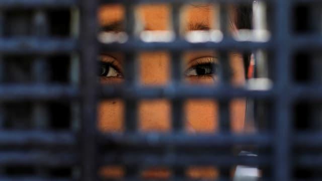 Gesicht durch den engmaschigen Zaun fotografiert.