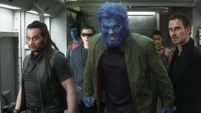 Mann mit blauem Kopf im Vordergrund umgeben von anderen Personen