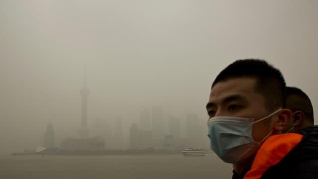 Ein Mann mit Gesichtsmaske vor der Smog-verhangenen Skyline von Schanghai.