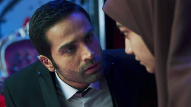 Filmszene: Ein Mann im Anzug redet eindringlich auf eine junge Frau mit Kopftuch ein.