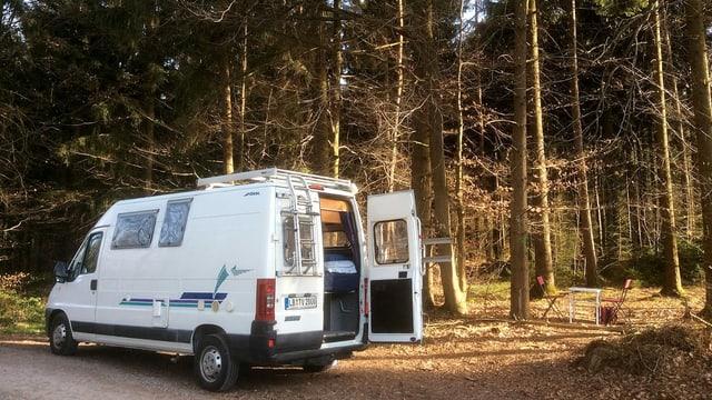 Ein Fiat Ducato Bus im Wald. Daben steht ein Campingtisch und 2 Stühle.