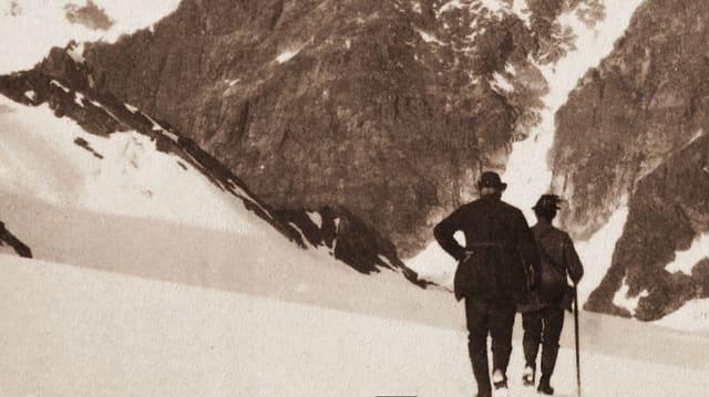 Zwei Bergsteiger auf verschneiter Bergeshöh.