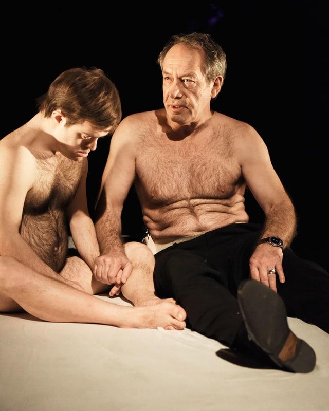 Theaterszene: Zwei Männer auf eienr Matratze, beide mit nacktem Oberkörper.