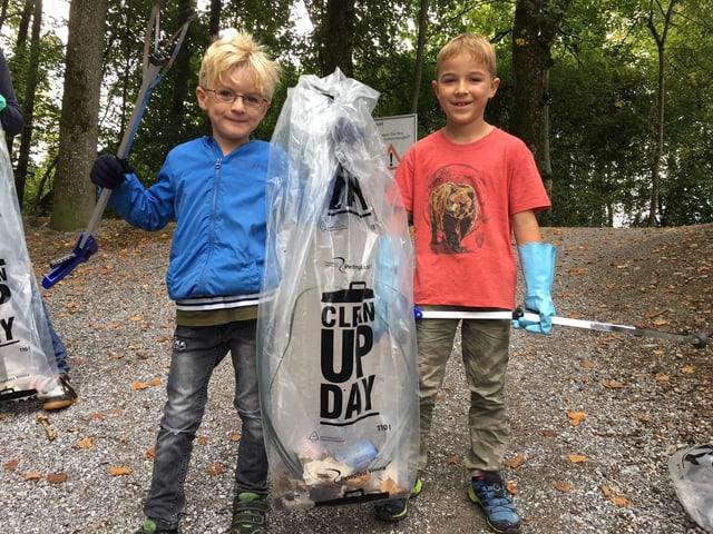 Kinder mit Abfallsäcken im Wald.