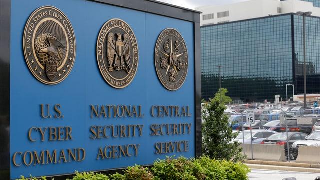 NSA-Logo vor einem Gebäude mit Parkplatz.