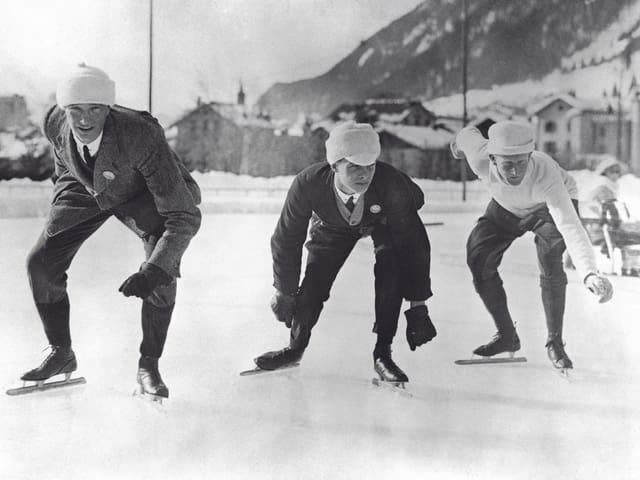 Drei Eiskunstläufer in Alltagskleidung, kurz vor dem Start.