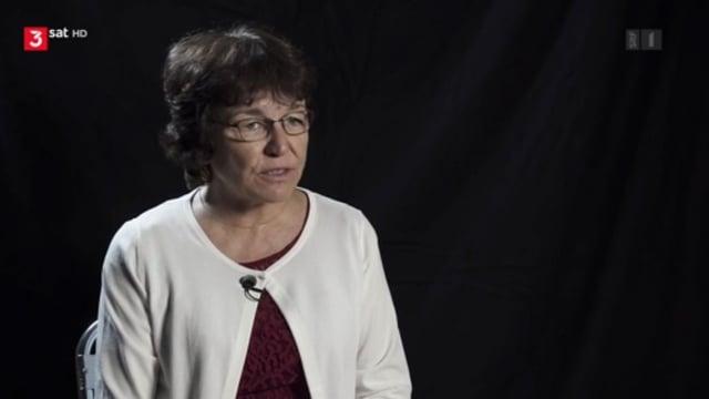 Eine Frau in weissem Jäckchen vor schwarzem Hintergrund