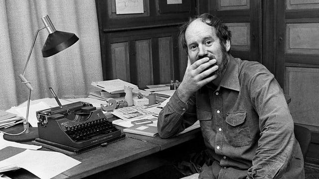 Franz Hohler an seinem Schreibtisch mit Schreibmaschine. Er hält sich die Hand vor den Mund.