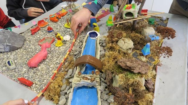 Ein Modell eines Spielplatzes mit einem Bach, das von Kindern gestaltet wurde.