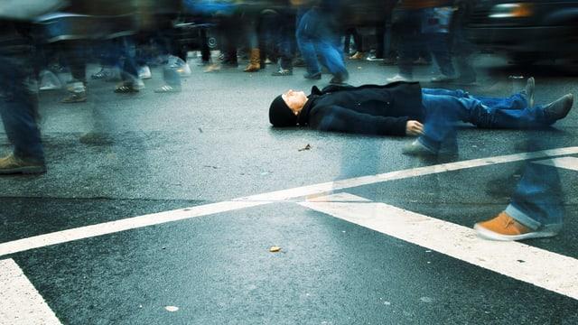 Ein Mann liegt am Boden auf der Strasse. Viele Menschen scheinen über ihn hinweg zu laufen.