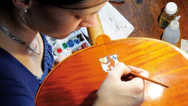 Eine junge Frau bemalt den Instrumentenboden eines Cellos mit einem Zunftwappen, das einen Affen zeigt.