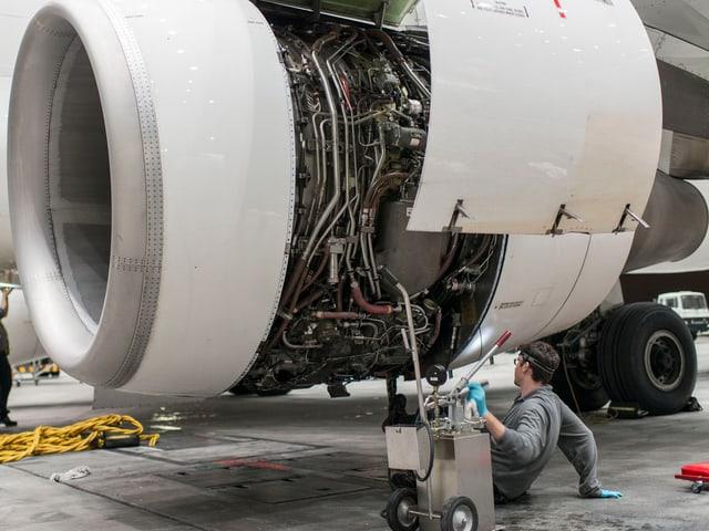 Ein Flugzeugtechniker bei der Wartung eines Triebwerks.