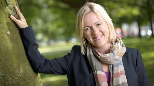 Die Autorin lehnt mit einem Arm gegen einen Baum und lacht in die Kamera.