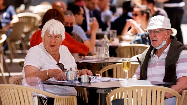 Älteres Paar trinkt Tee und ein Glas Weisswein.
