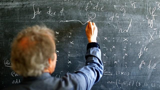 Mann steht vor einer Tafel mit mathematischen Zeichen und schreibt mit Kreide.