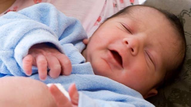 Ein neugeborenes Bébé in hellblauem Pyjama
