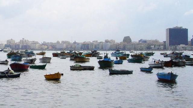 Blick vom Meer auf die Stadt, im Wasser sind zahlreiche kleine Boote.