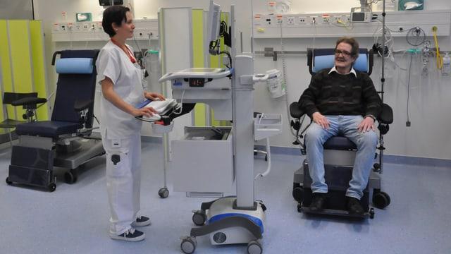 Ein Mann sitzt in einem Behandlungssessel und eine Pflegende steht an einem Computerwagen.