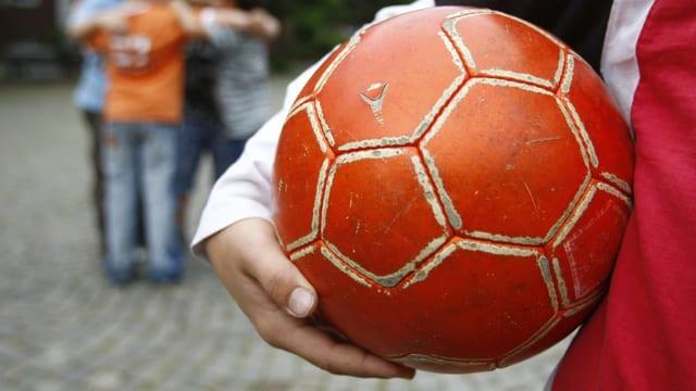 Ein Junge hält ein Ball in der Hand.