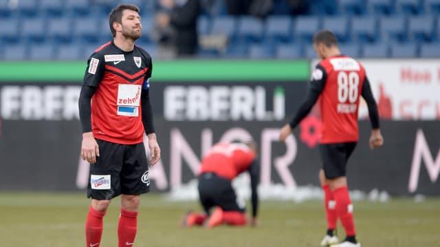 Lüscher enttäuscht, dahinter Spieler am Boden kniend.