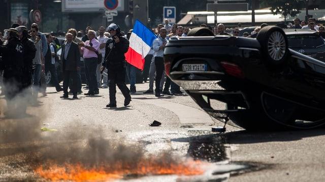 in auto sin il tetg, dasperas fieu, davostiers in policists e plirs demonstrants