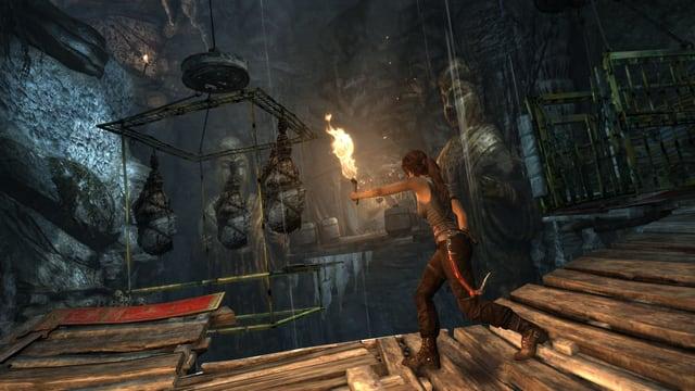 Ein Screenshot des Games «Tomb Raider» zeigt die Hauptfigur Lara Croft beim Rennen mit einer Fackel.