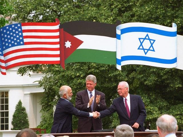 Rabin und Hussein reichen sich die Hand, darüber die Flaggen der Länder.