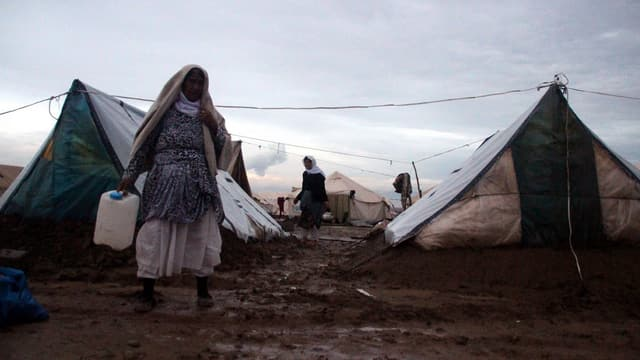 Eine Frau mit einem Wasserbehälter in der Hand läuft auf einem schlammigen Weg durch ein Flüchtlingslager