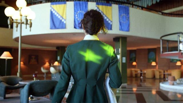 Eine Frau steht in einer Hotelhalle mit Europaflagge.