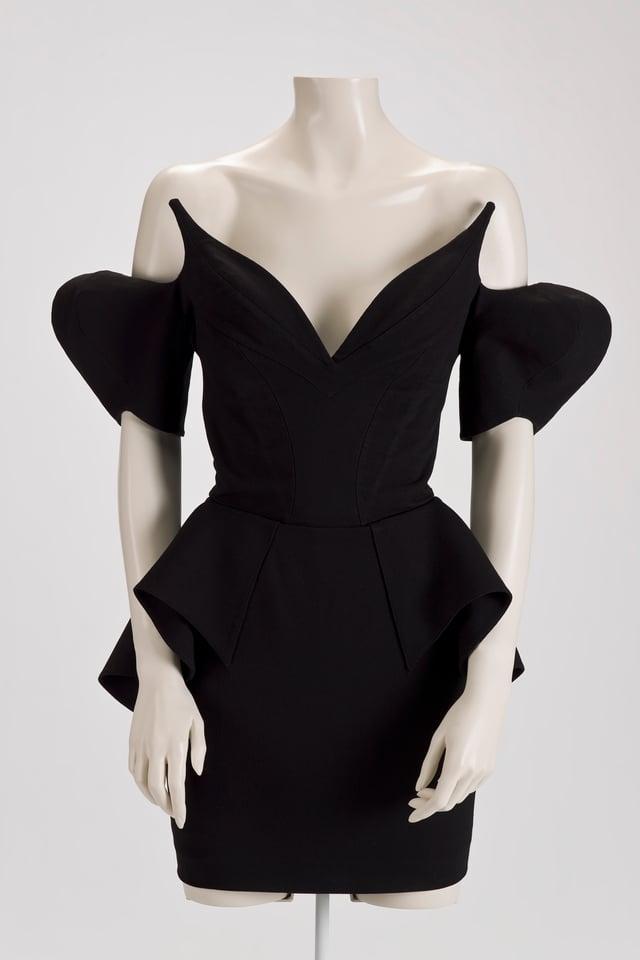 Ein schwarzes Kleid mit extravaganten Ärmeln ist an einer Schaufenster-Puppe ausgestellt.