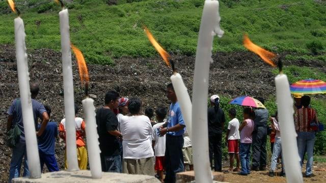 Kerzen sind im Vordergrund und im Hintergrund sihet man den Müllberg und Menschen