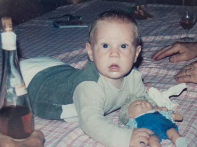 Christian Stucki als Baby auf einer Decke, mit Puppe