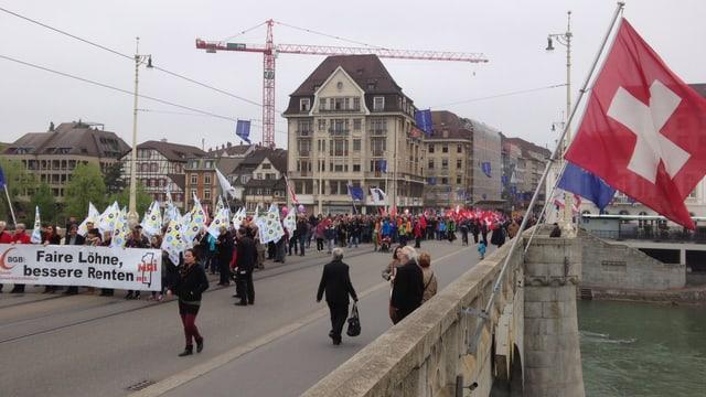 Ein Demonstrationszug auf der Mittleren Brücke, rechts eine Schweizer Fahne