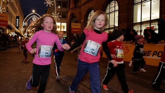 Drei  Kinder mit Startnummern auf den Sporttrikots