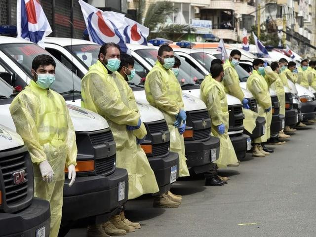Gesundheitspersonal vor Krankenwagen in Reih und Glied