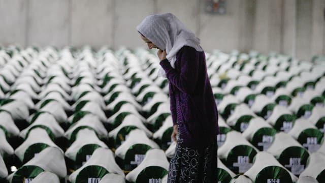 Eine Frau mit Kopftuch schaut auf den Boden. Im Hintergrund Särge, die mit Nummern versehen sind.