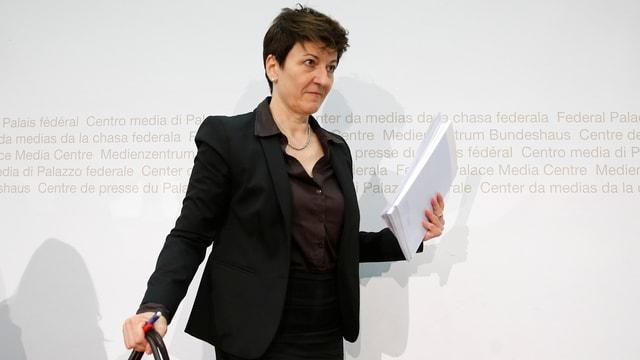 Della Valle stehend mit Unterlagen und Tasche im Raum für Medienkonferenzen des Bundeshauses in Bern.