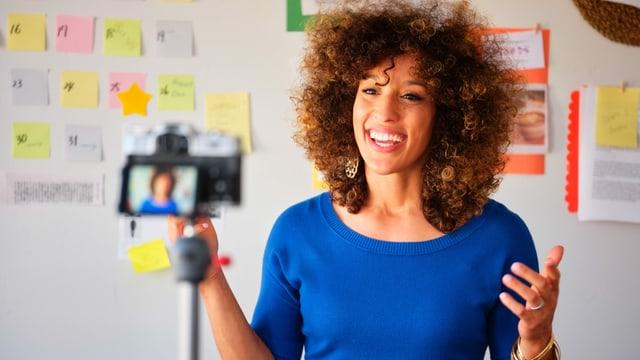 Eine Frau steht vor einer Kamera, im Hintergrund hängen verschiedene Lernmaterialien an der Wand