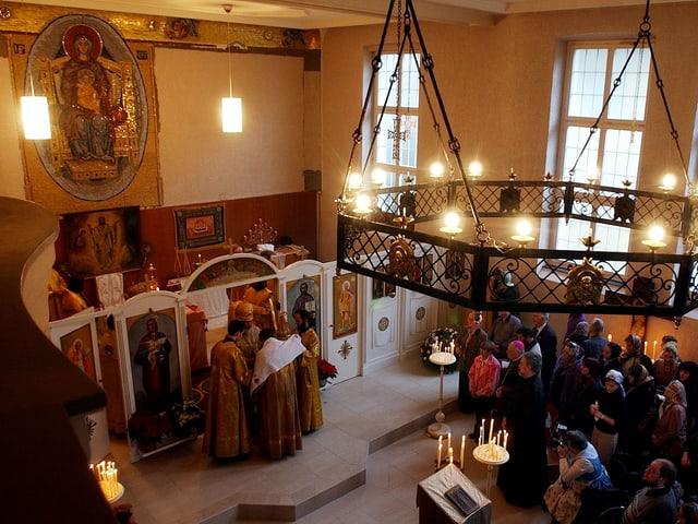 Geistliche stehen vor der Ikonostase im Altarraum.